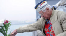 A Pearl Harbor survivor tosses flowers overboard in remembrance. (Photo credit: Official U.S. Navy Page Flickr)