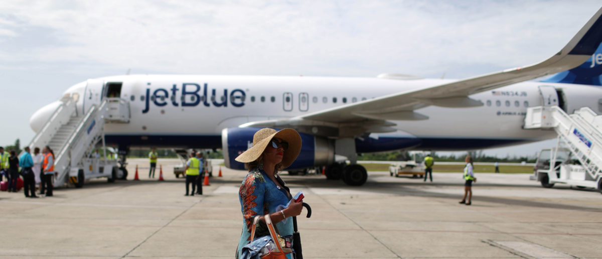 A passenger of a JetBlue aeroplane (seen on the foreground), the first commercial scheduled flight between the United States and Cuba in more than 50 years, walks away after landing at the Abel Santamaria International Airport in Santa Clara, Cuba, August 31, 2016. REUTERS/Alexandre Meneghini
