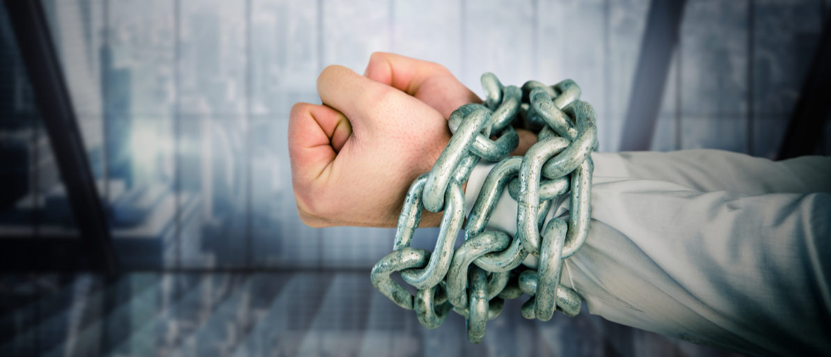 Digitally composite image of businessman hands bound in chains Shutterstock/ vectorfusianart