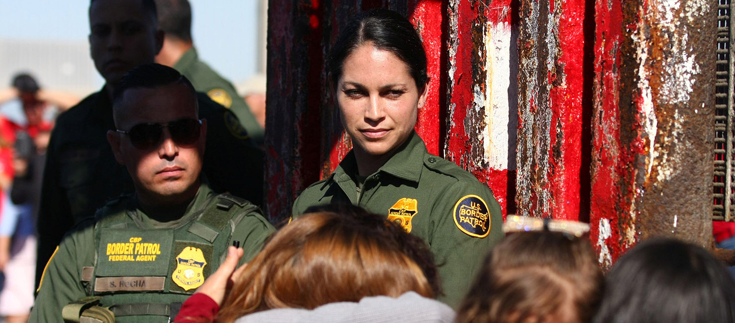 A member of the U.S. Border patrol agent watches as she open a single gate to allow families to hug and converse along the Mexico and U.S border in Tijuana, Mexico, November 18, 2017. REUTERS/Jorge Duenes