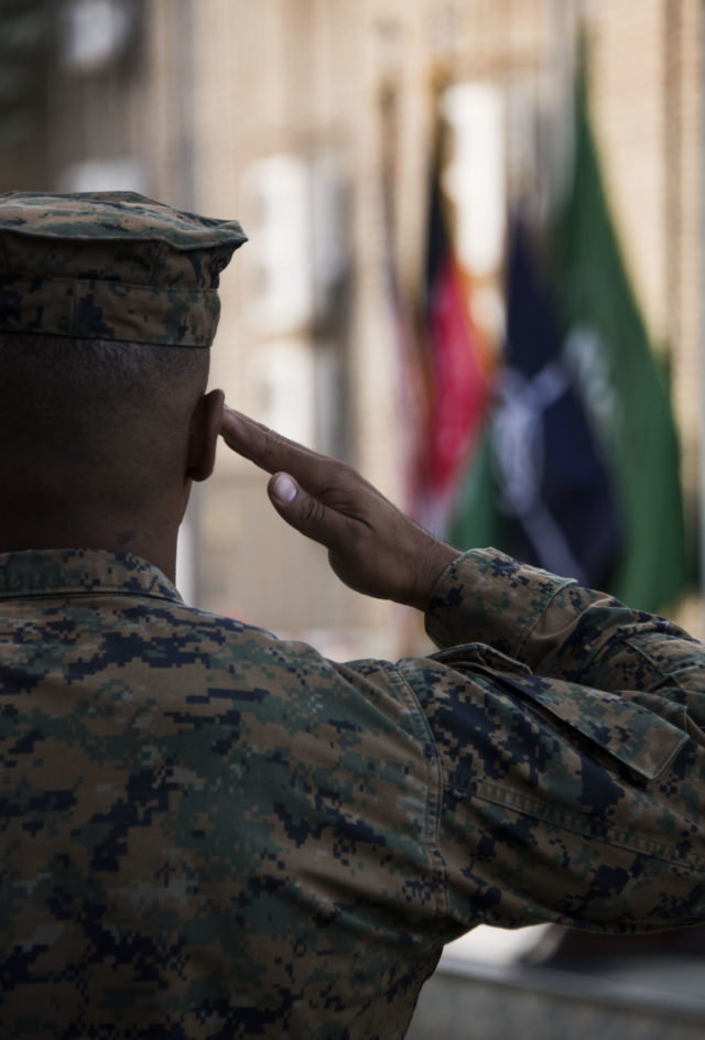A Marine salutes while the national anthem is played during a ceremony commemorating the U.S. Marine Corps 242nd birthday at Resolute Support Headquarters in Kabul, Afghanistan. (Hailey Sadler)