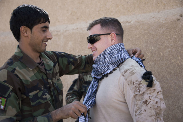 Capt. Richard Laszok receives a lesson on scarf-tying from a soldier in the Afghan National Army's 6th Kandak, 1st Brigade. The scar was a gift from Afghan Lt. Col. Mohibula (2nd Kandak, 4th Brigade Commander) who completed training at the Helmand Regional Training Center over the summer. (Hailey Sadler)