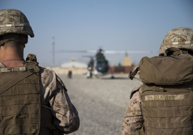 Marines wait to board their flight off of Camp Shorab, in Helmand Province. Marines in Iraq and Afghanistan routinely shoulder between approximately 60 and 120 pounds of gear, including body armor, equipment and weapons. (Hailey Sadler)