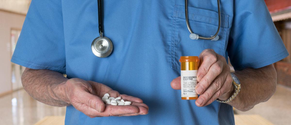Doctor Offering Patient Medication (ShutterStock/Steve Heap)