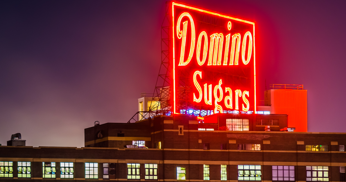 BALTIMORE - SEPTEMBER 17: The Domino Sugars Factory at night on September 17th, 2014 in Baltimore, Maryland. This factory is an important historic and tourist landmark in Baltimore. Shutterstock/ Jon Bilous