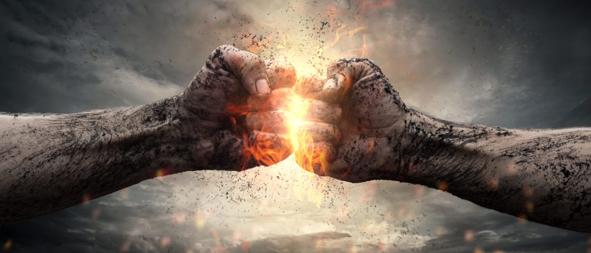 Fight, close up of two fists hitting each other over dark, dramatic sky. (Shutterstock/rangizzz)