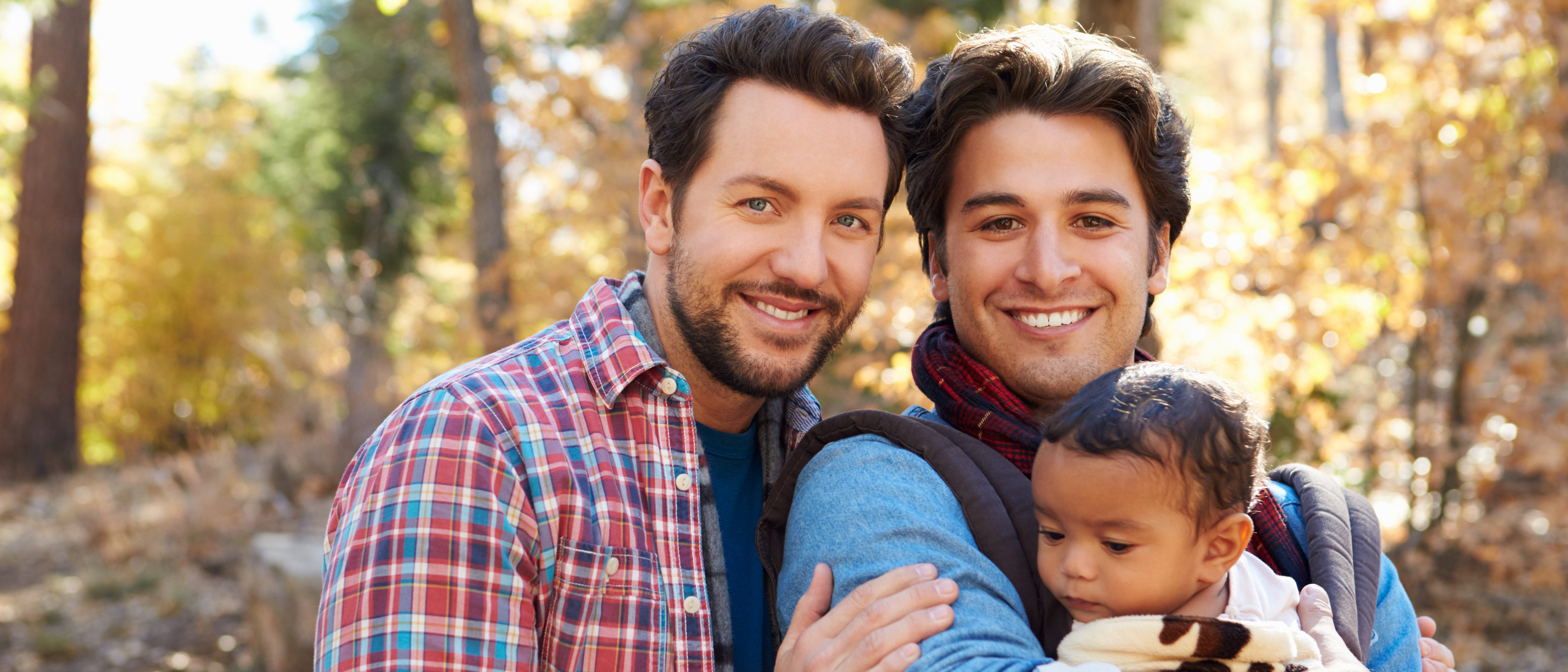 Gay Male Couple With Baby Walking Through Fall Woodland. (Shutterstock/Monkey Business News).