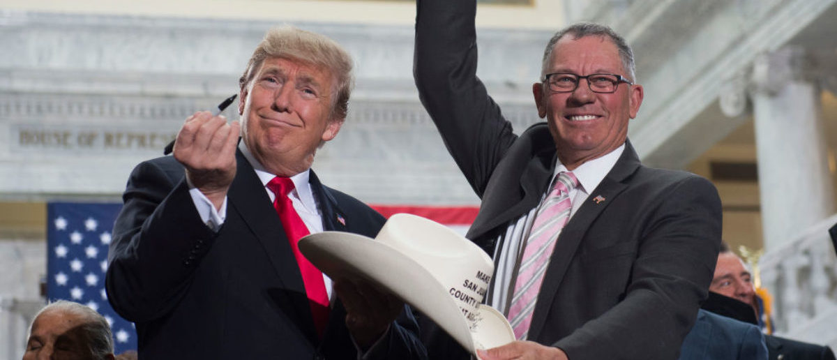 US President Donald Trump holds up a pen after signing the hat of Bruce Adams, Chairman of the San Juan County Commission, after signing a Presidential Proclamation shrinking Bears Ears and Grand Staircase-Escalante national monuments at the Utah State Capitol in Salt Lake City, Utah, December 4, 2017. / AFP PHOTO / SAUL LOEB (Photo credit should read SAUL LOEB/AFP/Getty Images)