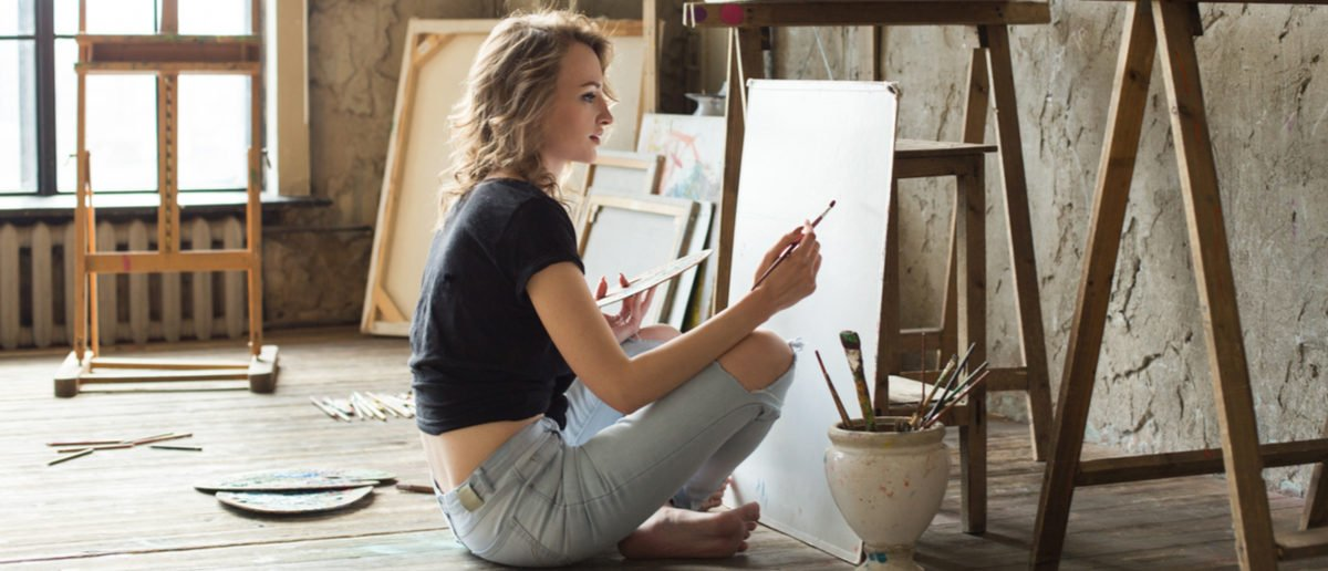 Woman painter sitting on the floor in front of the canvas and drawing. Artist studio interior. Drawing supplies, oil paints, artist brushes, canvas, frame. Workshop or art class. Creative concept Shutterstock/ Kate Aedon