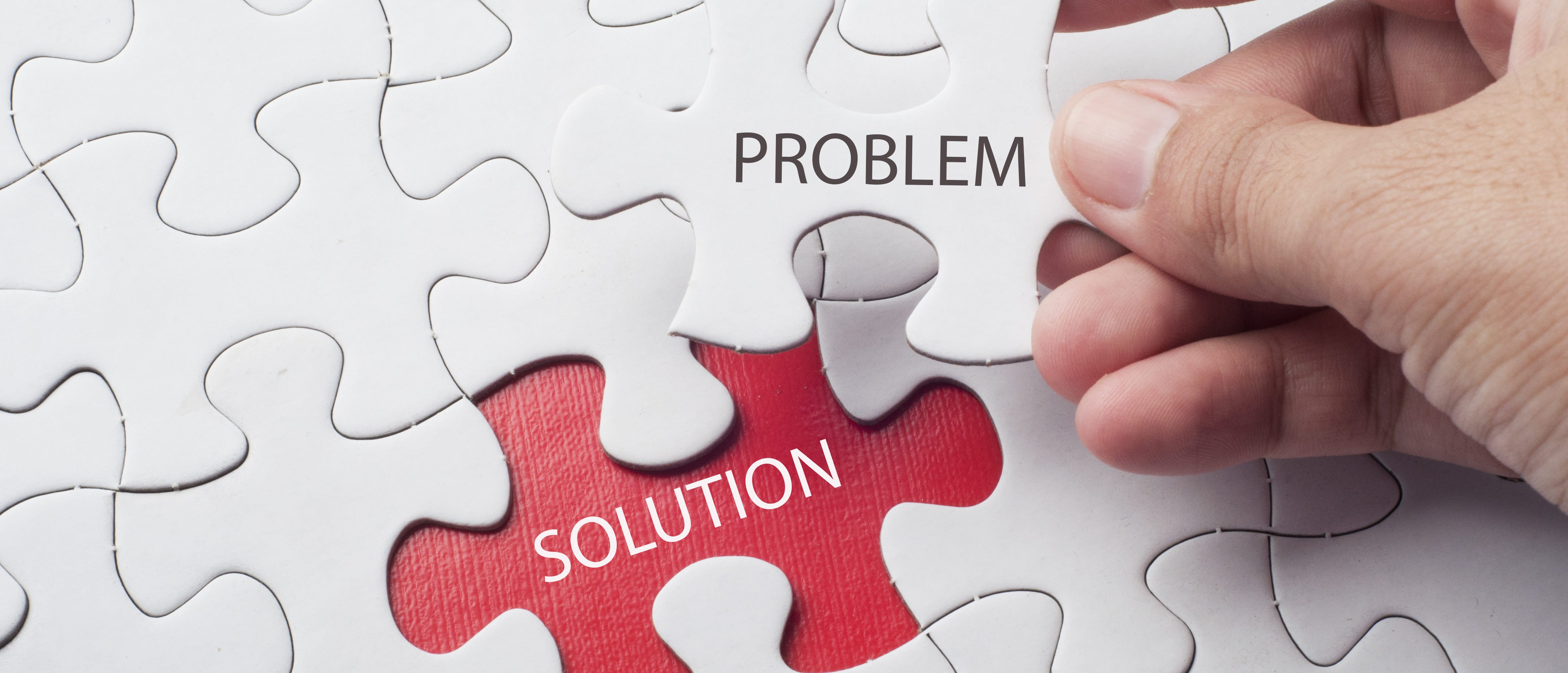 Hand holding piece of jigsaw puzzle with word problem & solution. (Shutterstock/Berhanuddin)