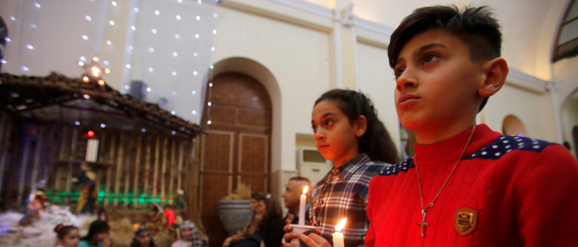 Iraqi Christians children carry candles during a mass on Christmas eve at St.George Chaldean Church in Baghdad, Iraq December 24, 2017. REUTERS/Khalid al Mousily