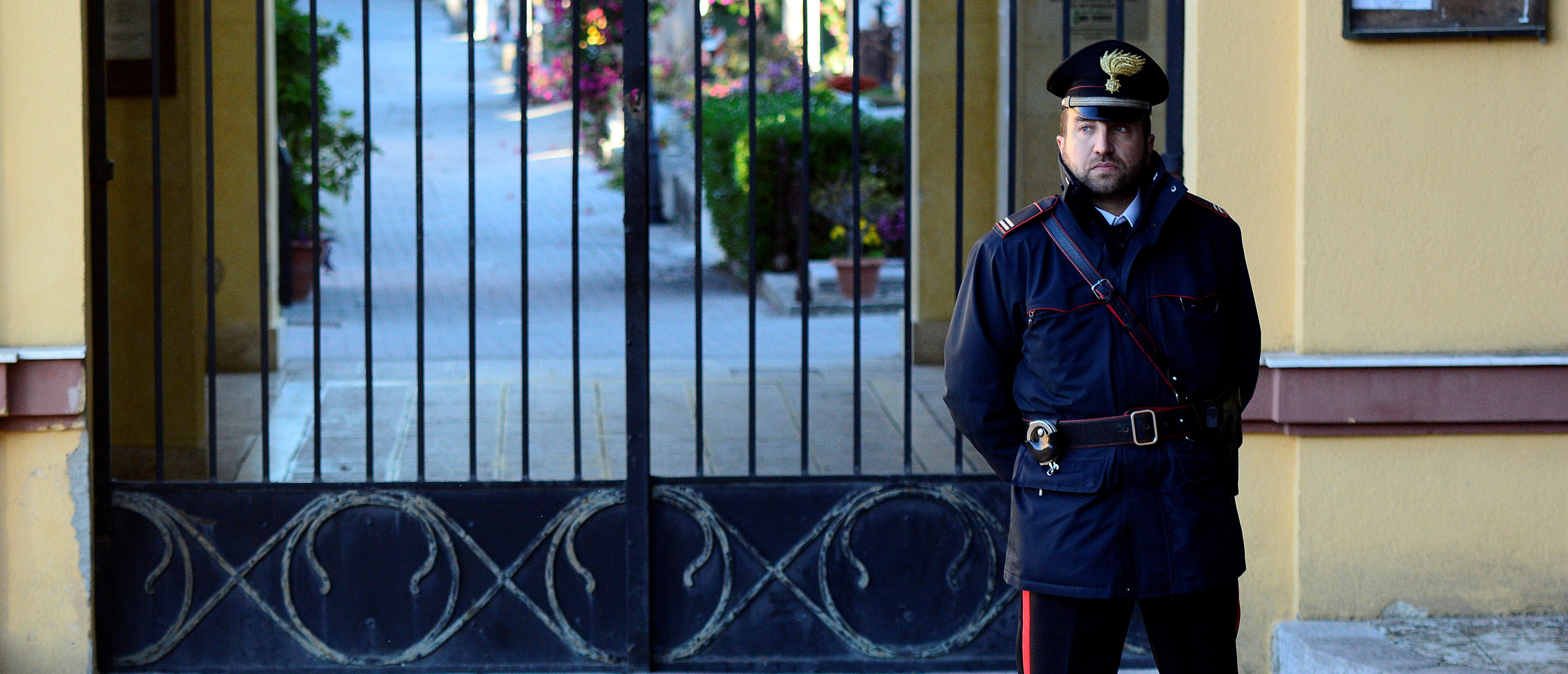 An Italian Carabinieri police officer patrols outside the cemetery in Corleone, Italy November 22, 2017. REUTERS/Guglielmo Mangiapane