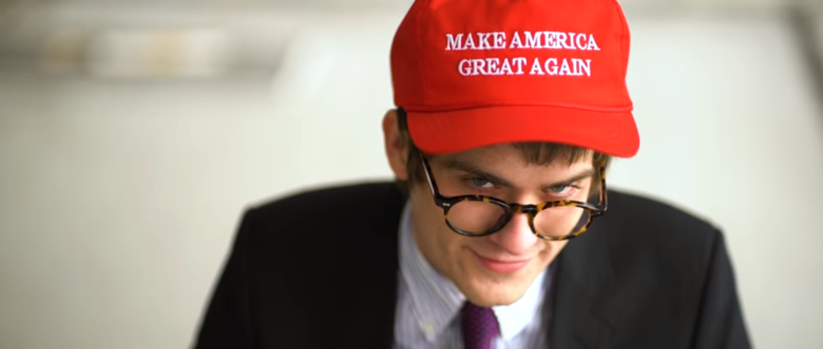 A MAGA hat-sporting Lucian Wintrich flashes a wry grin to Elite Daily. (Photo Credit: YouTube/Elite Daily)
