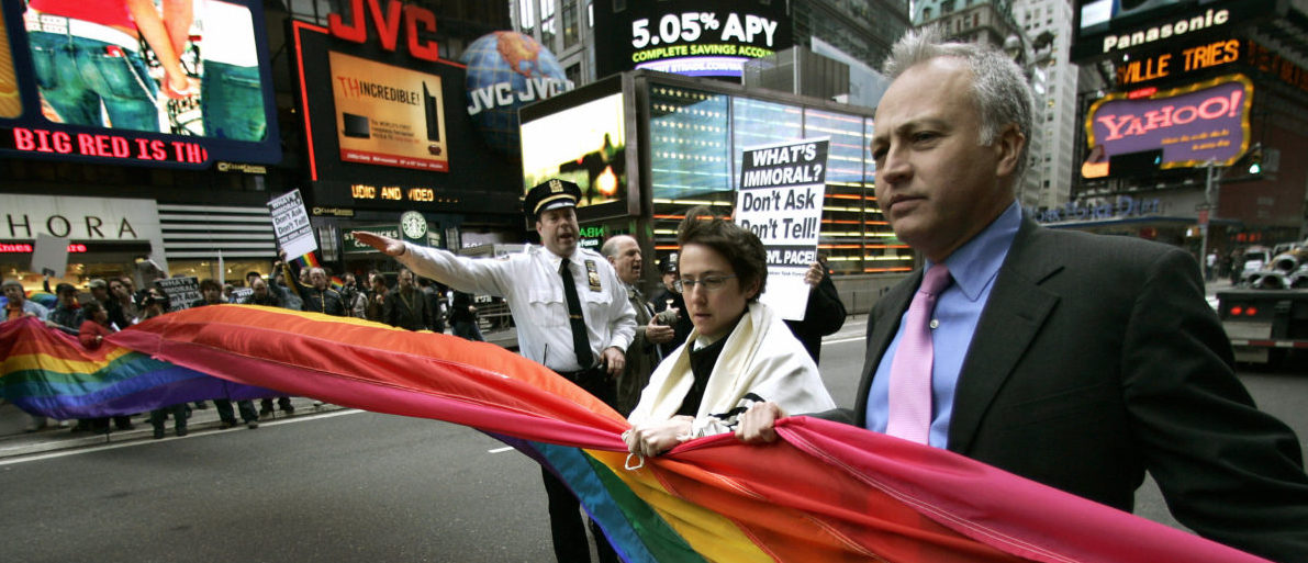 """New York, UNITED STATES: Matt Foreman,Executive Director of the National Gay and Lesbian Task Force and Rabbi Sharon Kleinbaum block traffic with a banner moments before they get arrested in the middle of Broadway in Times Square during a protest by ACT UP (AIDS Coaltion to Unleash Power) in New York 15 March 2007. The group protested at the Times Square Military recruitment center against the remarks made about gays by US Joint Chiefs of Staff Chairman General Peter Pace. In an interview with the Chicago Tribune's editorial board 13 March 2007, Pace said he supported the """"Don't Ask, Don't Tell"""" military policy because homosexual acts are """"immoral."""" He also likened homosexuality to adultery, which also is forbidden under US military law.     (Photo: TIMOTHY A. CLARY/AFP/Getty Images)"""