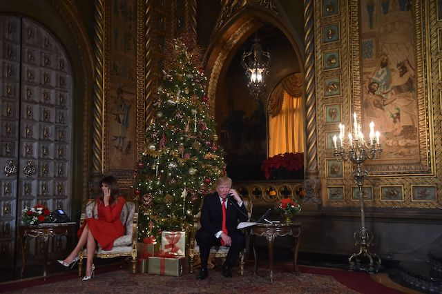 "US President Donald J. Trump and the First Lady Melania Trump participate in NORAD Santa Tracker phone calls at the Mar-a-Lago resort in Palm Beach, Florida on December 24, 2017. ""NORAD Tracks Santa"" is an annual Christmas-themed entertainment program, which has existed since 1955, produced under the auspices of the North American Aerospace Defense Command. / AFP PHOTO / Nicholas Kamm (Photo credit should read NICHOLAS KAMM/AFP/Getty Images)"