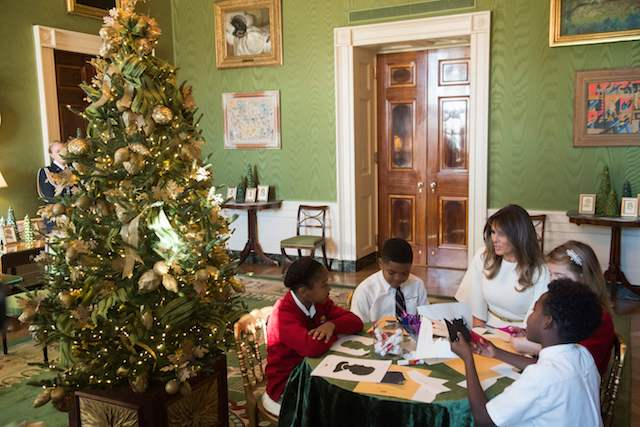 US First Lady Melania Trump speaks with children as they make holiday decorations in the Green Room as she tours Christmas decorations at the White House in Washington, DC, November 27, 2017. / AFP PHOTO / SAUL LOEB (Photo credit should read SAUL LOEB/AFP/Getty Images)