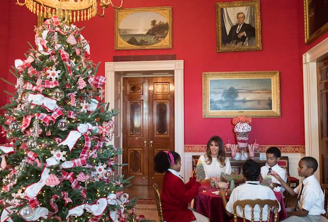 US First Lady Melania Trump speaks with children as they make holiday decorations in the Red Room as she tours Christmas decorations at the White House in Washington, DC, November 27, 2017. / AFP PHOTO / SAUL LOEB (Photo credit should read SAUL LOEB/AFP/Getty Images)