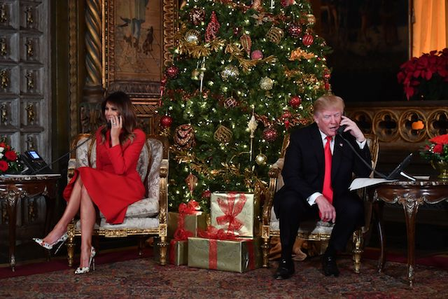 US President Donald J. Trump and the First Lady Melania Trump participate in NORAD Santa Tracker phone calls at the Mar-a-Lago resort in Palm Beach, Florida on December 24, 2017. / AFP PHOTO / Nicholas Kamm (Photo credit should read NICHOLAS KAMM/AFP/Getty Images)