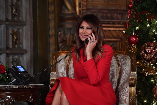 "First Lady Melania Trump participates in NORAD Santa Tracker phone calls at the Mar-a-Lago resort in Palm Beach, Florida on December 24, 2017. ""NORAD Tracks Santa"" is an annual Christmas-themed entertainment program, which has existed since 1955, produced under the auspices of the North American Aerospace Defense Command. / AFP PHOTO / Nicholas Kamm (Photo credit should read NICHOLAS KAMM/AFP/Getty Images)"
