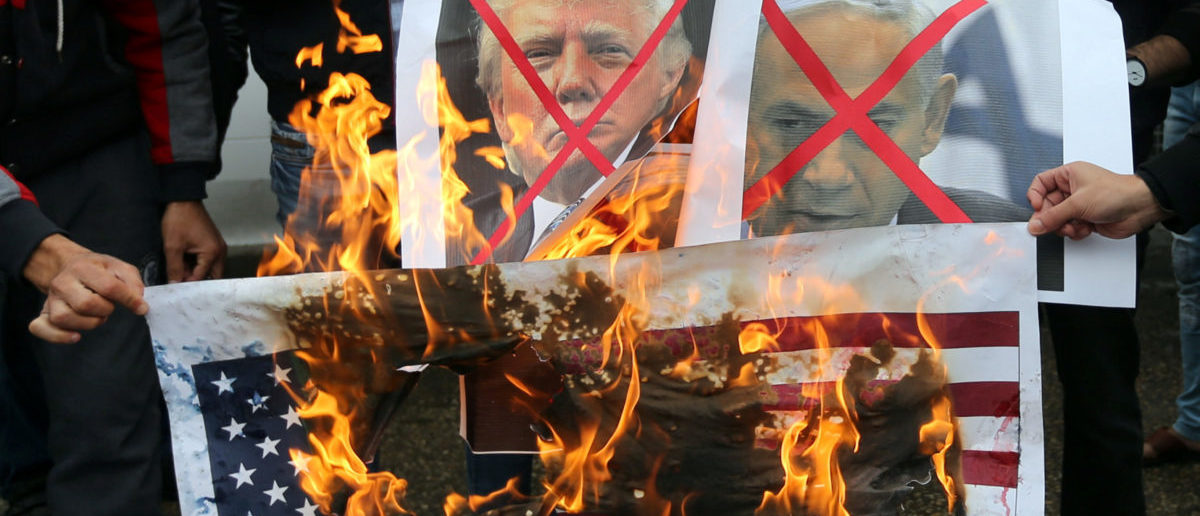 Palestinians burn posters depicting Israeli Prime Minister Benjamin Netanyahu and U.S. President Donald Trump during a protest against the U.S. intention to move its embassy to Jerusalem and to recognize the city of Jerusalem as the capital of Israel, in Rafah in the southern Gaza Strip December 6, 2017. REUTERS/Ibraheem Abu Mustafa