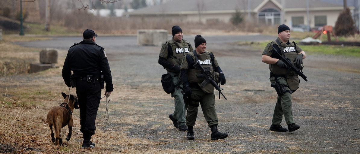 Police SWAT officers and a K-9 team search for Bradley William Stone, 35, an Iraq war veteran suspected of fatally shooting and stabbing six family members in Pennsburg, Pennsylvania December 16, 2014. The search for Stone was focused around his hometown of Pennsburg, about 50 miles (80 km) northwest of Philadelphia, where residents were advised to stay inside with their doors locked, Montgomery County District Attorney Risa Vetri Ferman told a news conference. REUTERS/Brad Larrison