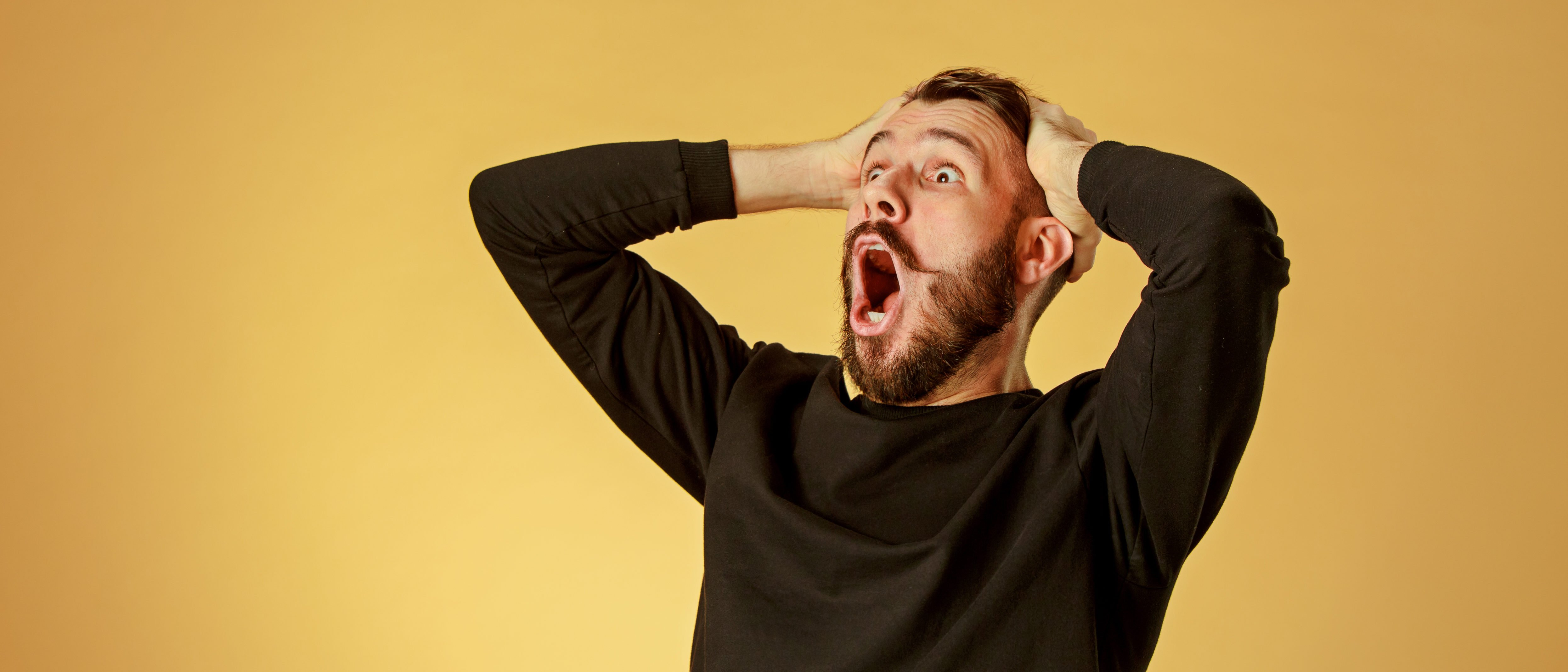 Portrait of young man with shocked facial expression. (Shutterstock/Master1305)