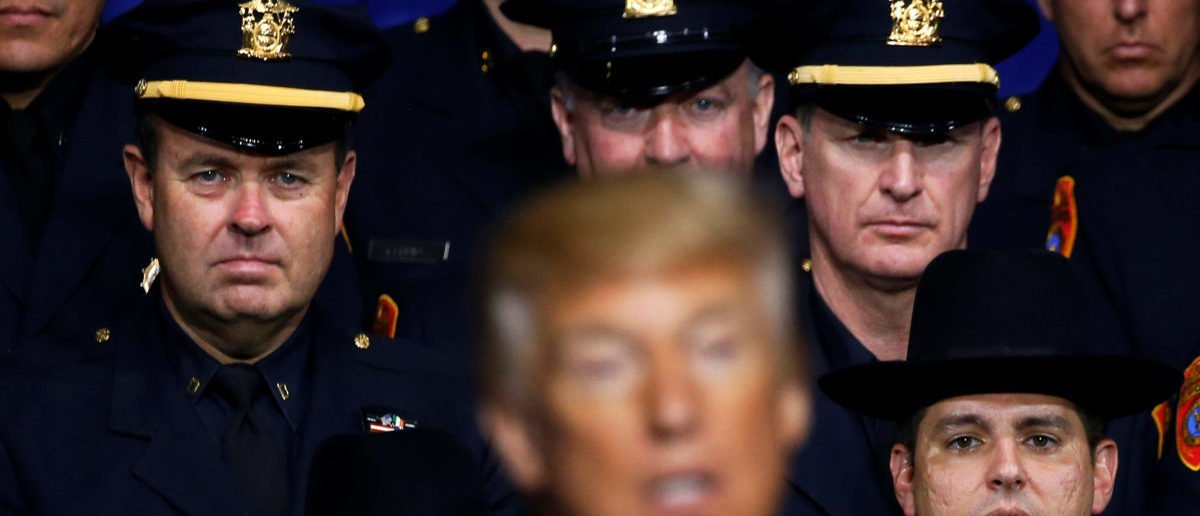 Police officers look on as U.S. President Donald Trump delivers remarks about his proposed U.S. government effort against the street gang Mara Salvatrucha, or MS-13, to a gathering of federal, state and local law enforcement officials in Brentwood, New York, U.S. July 28, 2017. REUTERS/Jonathan Ernst - RC1269FD8FB0