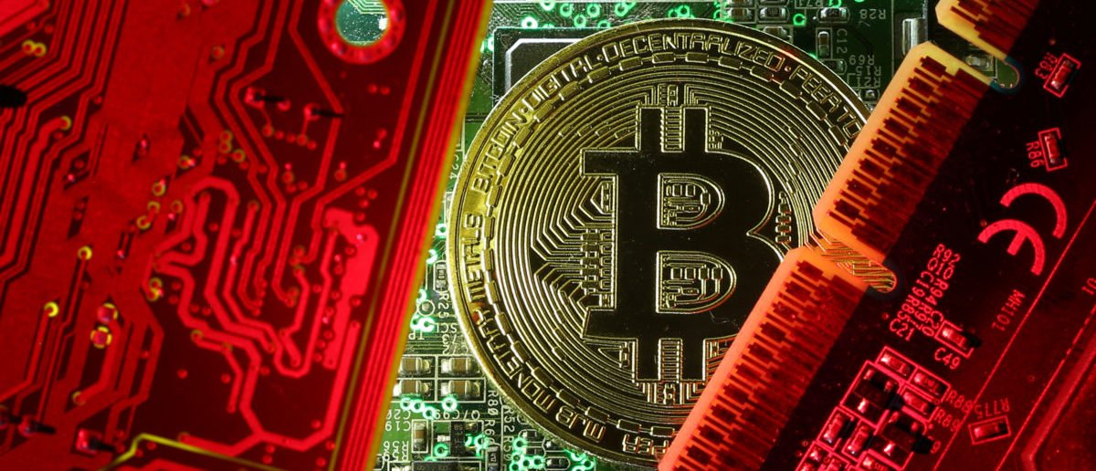 FILE PHOTO: A coin representing the bitcoin cryptocurrency is seen on computer circuit boards in this illustration picture, October 26, 2017. REUTERS/Dado Ruvic/File Photo