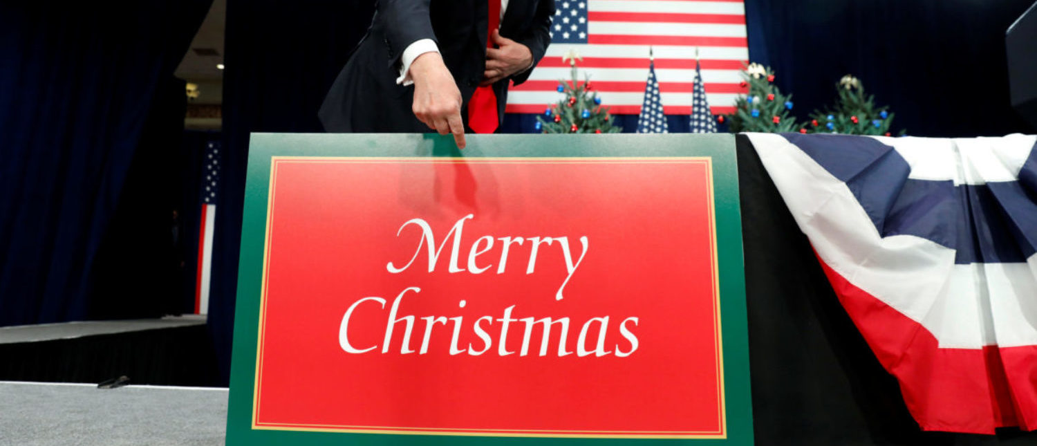 "FILE PHOTO: U.S. President Donald Trump points to a large ""Merry Christmas"" card on the stage as he arrives to deliver remarks on tax reform in St. Louis, Missouri, U.S. November 29, 2017. REUTERS/Kevin Lamarque/File Photo"