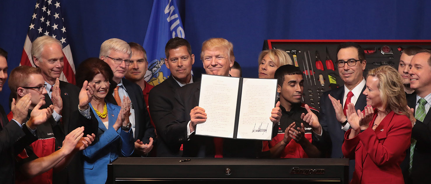 President Donald Trump signs an executive order to try to bring jobs back to American workers and revamp the H-1B visa guest worker program during a visit to the headquarters of tool manufacturer Snap-On on April 18, 2017 in Kenosha, Wisconsin.  (Photo by Scott Olson/Getty Images)