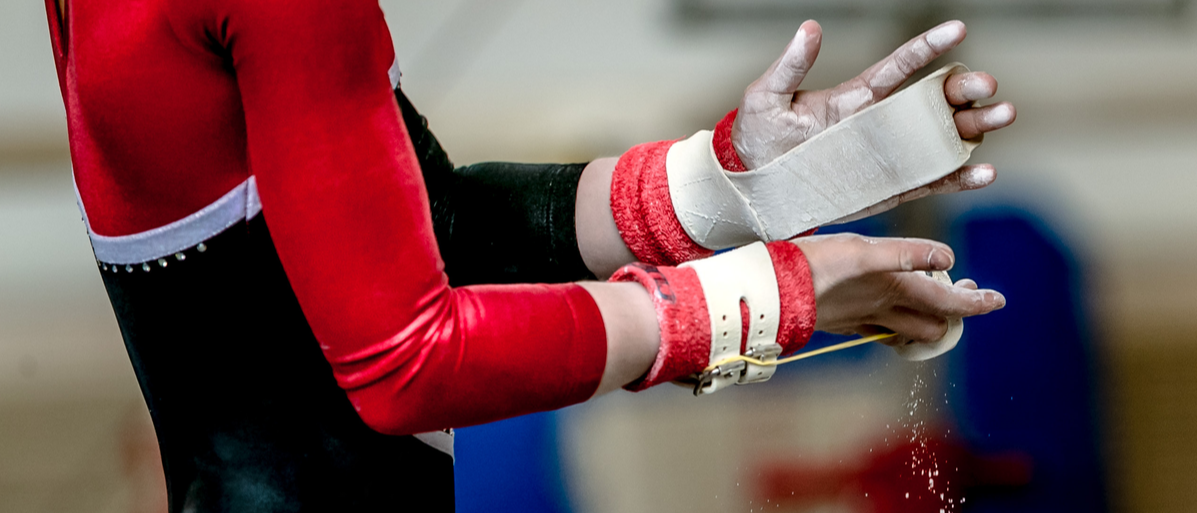 hands of girl in gymnast grips before performing on horizontal bar Shutterstock/ sportpoint