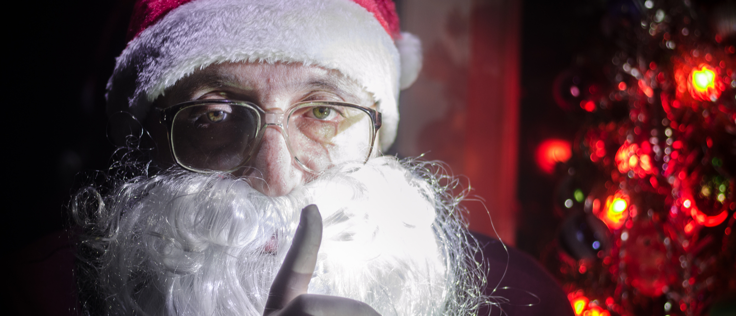 Santa Claus shushes the camera, fearing for his life. (Shutterstock/Ilkin Zeferli)