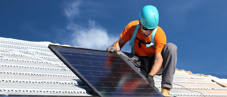Man installs alternative energy photovoltaic solar panels on roof Federico Rostagno/Shutterstock)
