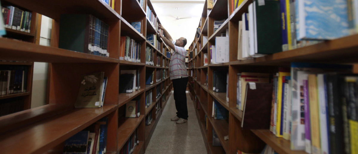 "An Iraqi librarian sorts books on the shelves of the central library in Basra, about 420 km (261 miles) southeast of Baghdad, March 18, 2013. Ten years ago this week, British forces entered Iraq's second city, Basra, as part of the U.S.-led invasion of the country. Known locally as a cultural hero, librarian Alia Baqer moved to rescue the contents of Basra's central library before everything was lost. ""At the beginning of the war on Iraq, the governor (of Basra) took the library over as a headquarters for himself and his guards, mounting machine guns on top of the building. So, we asked the governor if we could take the important books to our homes, but he rejected the idea. Eventually we took the responsibility ourselves to transfer the books, without the governor's approval,"" Baqer said. Baqer moved about 30,000 books out of the city's central library to a neighbouring restaurant and later to her home, before the looting and burning of the library during the first days of the U.S.-invasion of Iraq began. REUTERS/Atef Hassan"