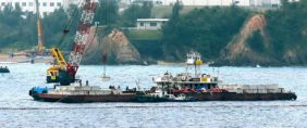 A crane barge works in the Henoko coastal area in Nago, Okinawa prefecture on February 6, 2017. The Japanese government on February 6 resumed work on building a controversial US airbase on Okinawa island, sparking angry protests and scuffles with police. Jiji Press/AFP/Getty Images.