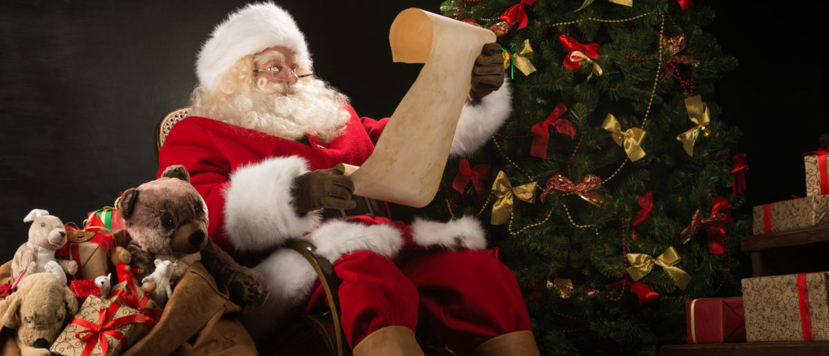 Portrait of happy Santa Claus sitting at his room at home near Christmas tree and big sack and reading Christmas letter or wish list. (Credit: Shutterstock/ Milles Studio)