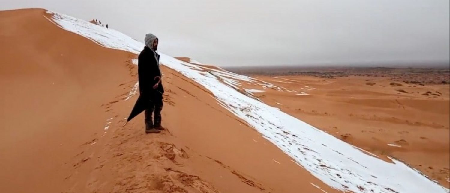 A man looks at at a snow-covered slope in the Sahara, Ain Sefra, Algeria, January 7, 2018 in this picture obtained from social media. Hamouda Ben Jerad/via REUTERS