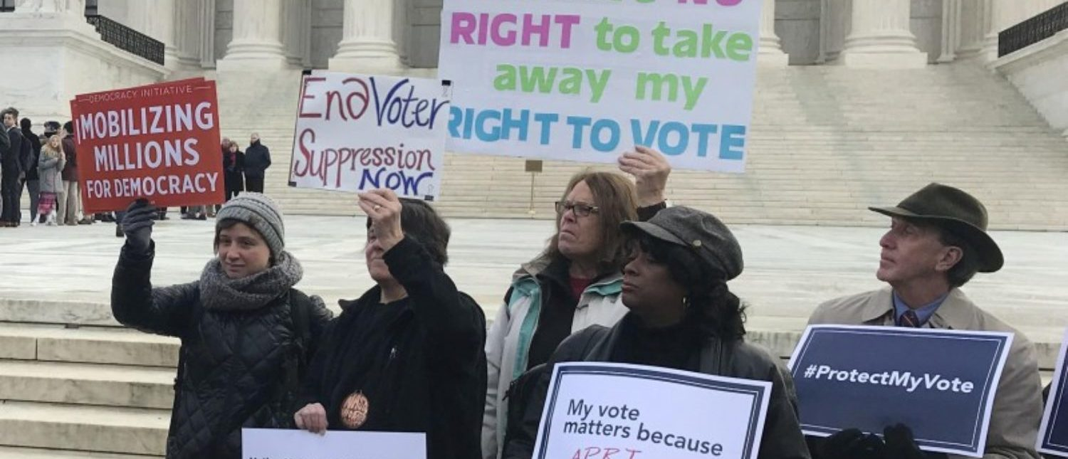 Activists rally outside the U.S. Supreme Court ahead of arguments in a key voting rights case involving a challenge to the OhioÕs policy of purging infrequent voters from voter registration rolls, in Washington, U.S., January 10, 2018. REUTERS/Lawrence Hurley