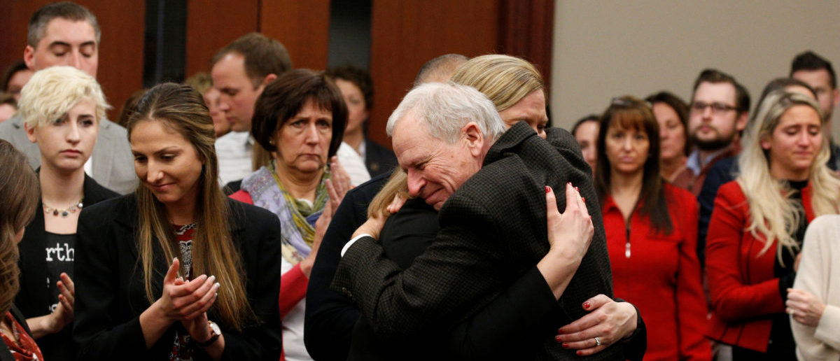 Prosecutor Angela Povilaitis is embraced by Michigan State University Police Chief Jim Dunlap at the conclusion of the sentencing hearing for Larry Nassar, a former team USA Gymnastics doctor who pleaded guilty in November 2017 to sexual assault charges, in Lansing, Michigan, U.S., January 24, 2018. REUTERS/Brendan McDermid