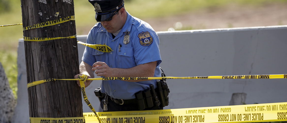 A police officer creates a cordon at the site of a derailed Amtrak train in Philadelphia, Pennsylvania May 13, 2015. Rescue workers searched through the debris on Wednesday for more victims of an Amtrak passenger train wreck in Philadelphia that killed six people and injured scores others as investigators sought to determine the cause of the derailment. Authorities said they did not know what caused the New York City-bound train carrying 243 people to derail at about 9:30 p.m. EDT Tuesday (0130 GMT Wednesday). The accident left rail cars mangled, ripped open and strewn upside down in the city's Port Richmond neighborhood along the Delaware River. REUTERS/Mike Segar - GF10000093215