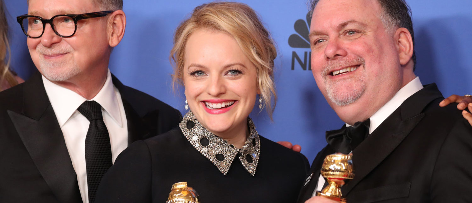 "75th Golden Globe Awards – Photo Room – Beverly Hills, California, U.S., 07/01/2018 – Actress Elisabeth Moss (C) and producers Warren Littlefield (L) and Bruce Miller pose with the awards they won for ""The Handmaid's Tale"" for Best Television Series - Drama. REUTERS/Lucy Nicholson"
