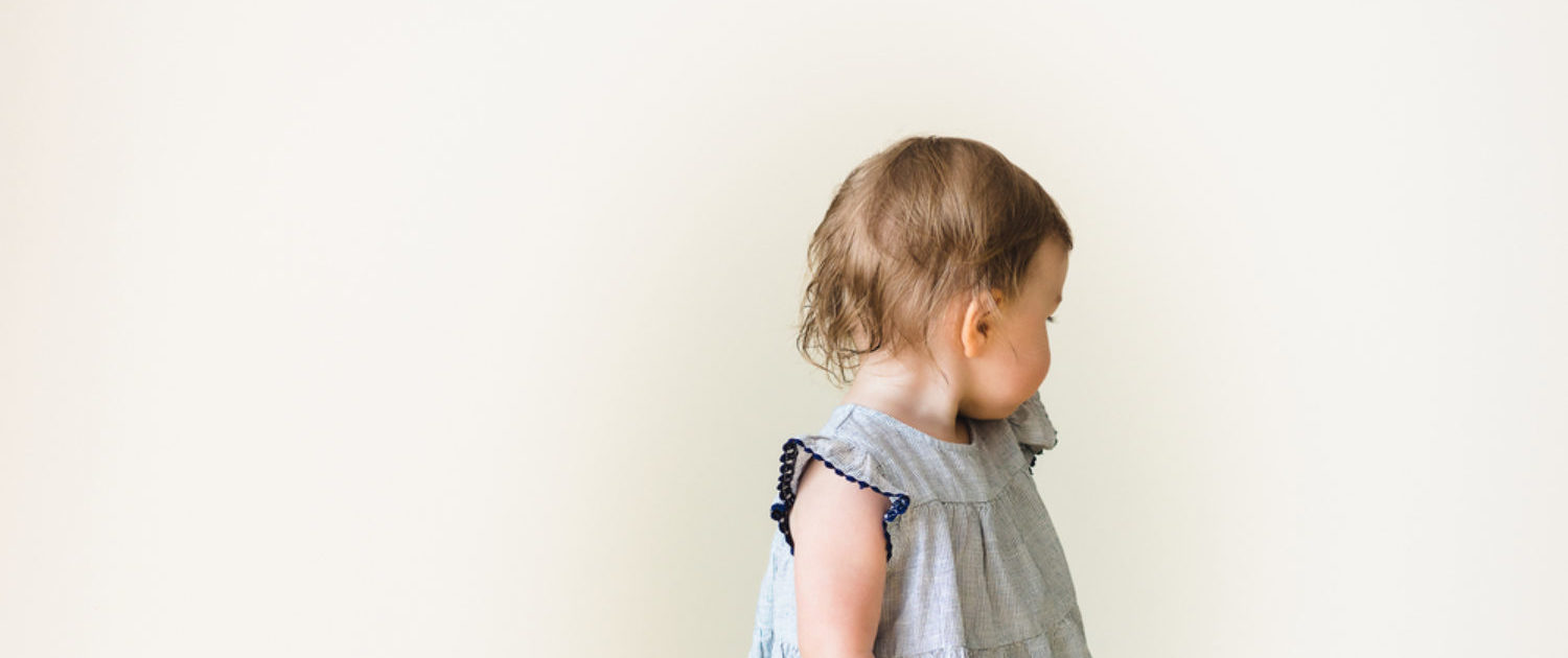 A baby girl is wearing a dress. (Photo: Shutterstock/riggleton)