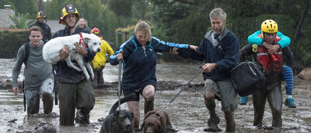Emergency personnel evacuate local residents and their dogs through flooded waters after a mudslide in Montecito, California, U.S. January 9, 2018.   Kenneth Song/Santa Barbara News-Press via REUTERS