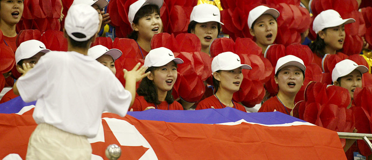 North Koreans sing prior to the start of the women's weight lifting final at the 14th Asian Games in Pusan October 1, 2002. Their beauty and graceful manners have made the North Korean official cheerleaders heartthrobs in South Korea - but like their communist homeland, the women are fenced off from the rest of the world. REUTERS/Zainal Abd Halim