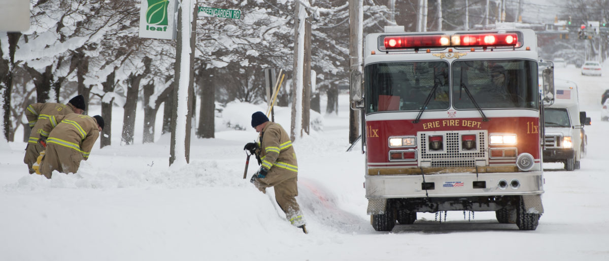 Firefighters remove snow from around fire hydrants on West 8th street in Erie,
