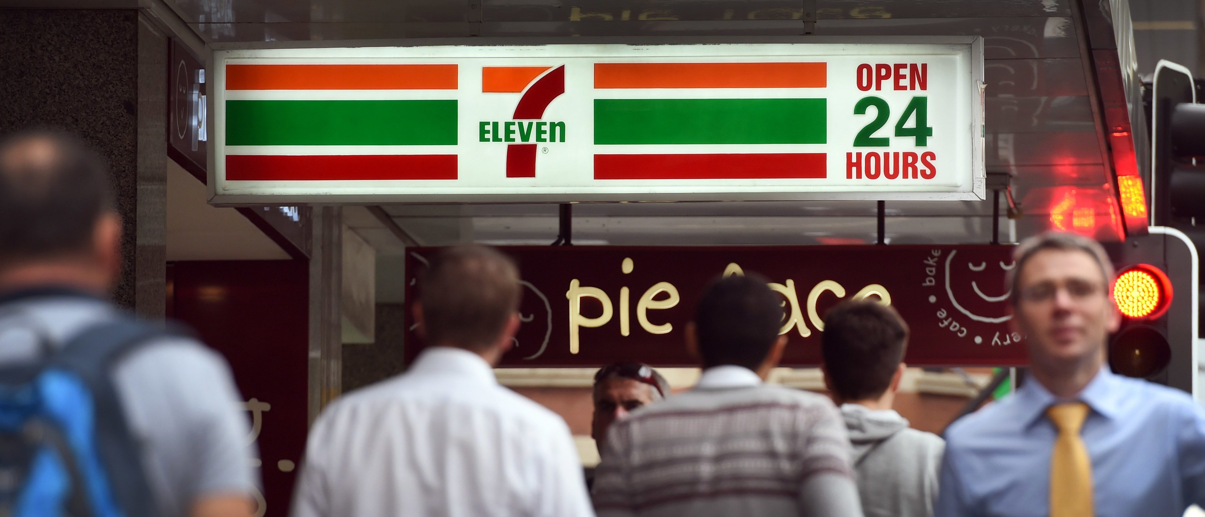 People walk past a 7-Eleven convenience store in Sydney's central business district on September 30, 2015.The chairman and chief executive of 7-Eleven convenience stores in Australia resigned on September 30, following allegations that franchises systematically underpaid workers. WILLIAM WEST/AFP/Getty Images