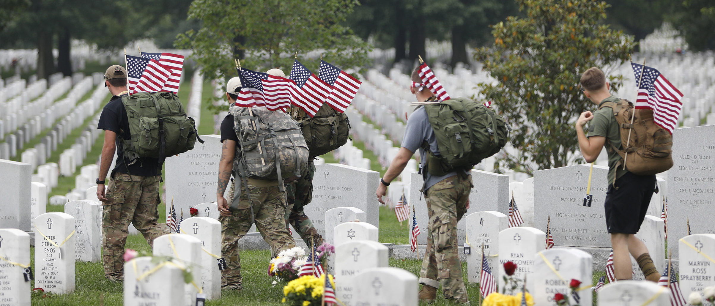 ARLINGTON, VA - MAY 29: Visitors walk amongst the gravestones at Arlington National Cemetery in Arlington, Virginia May 29, 2017. Thousands folk to the cemetery on Memorial Day to pay tribute to fallen service members. (Photo by Aaron P. Bernstein/Getty Images)