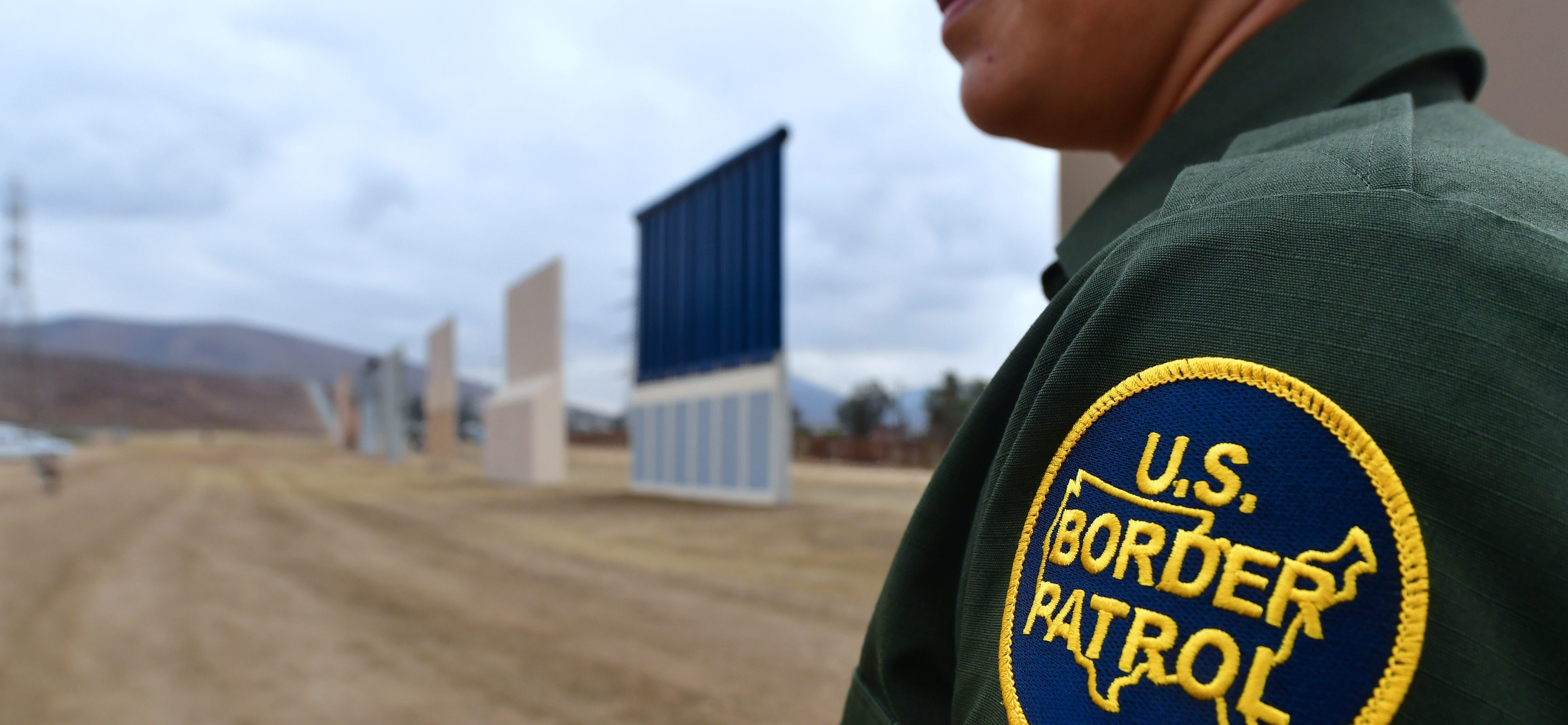 US Border Patrol officer Tekae Michael stands near prototypes of US President Donald Trump's proposed border wall on November 1, 2017 in San Diego, California.