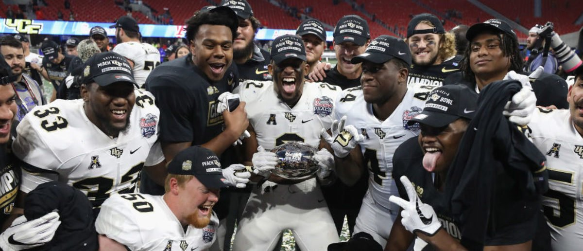 The UCF Knights celebrate defeating the Auburn Tigers 34-27 to win the Chick-fil-A Peach Bowl at Mercedes-Benz Stadium on January 1, 2018 in Atlanta. (Photo by Streeter Lecka/Getty Images)