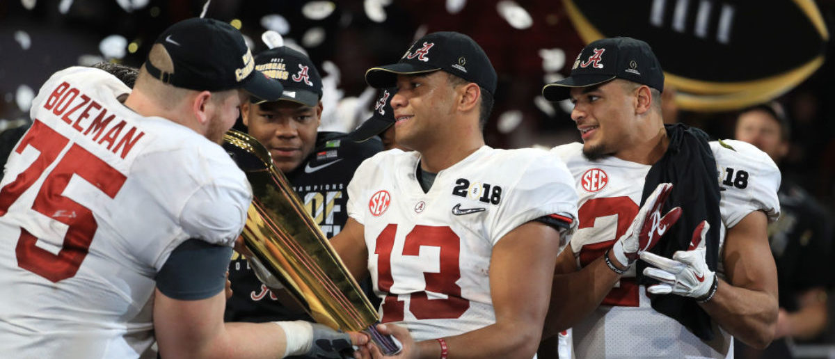Tua Tagovailoa #13 of the Alabama Crimson Tide holds the trophy while celebrating with his team after defeating the Georgia Bulldogs in overtime to win the CFP National Championship presented by AT&T at Mercedes-Benz Stadium on January 8, 2018 in Atlanta. (Photo by Mike Ehrmann/Getty Images)